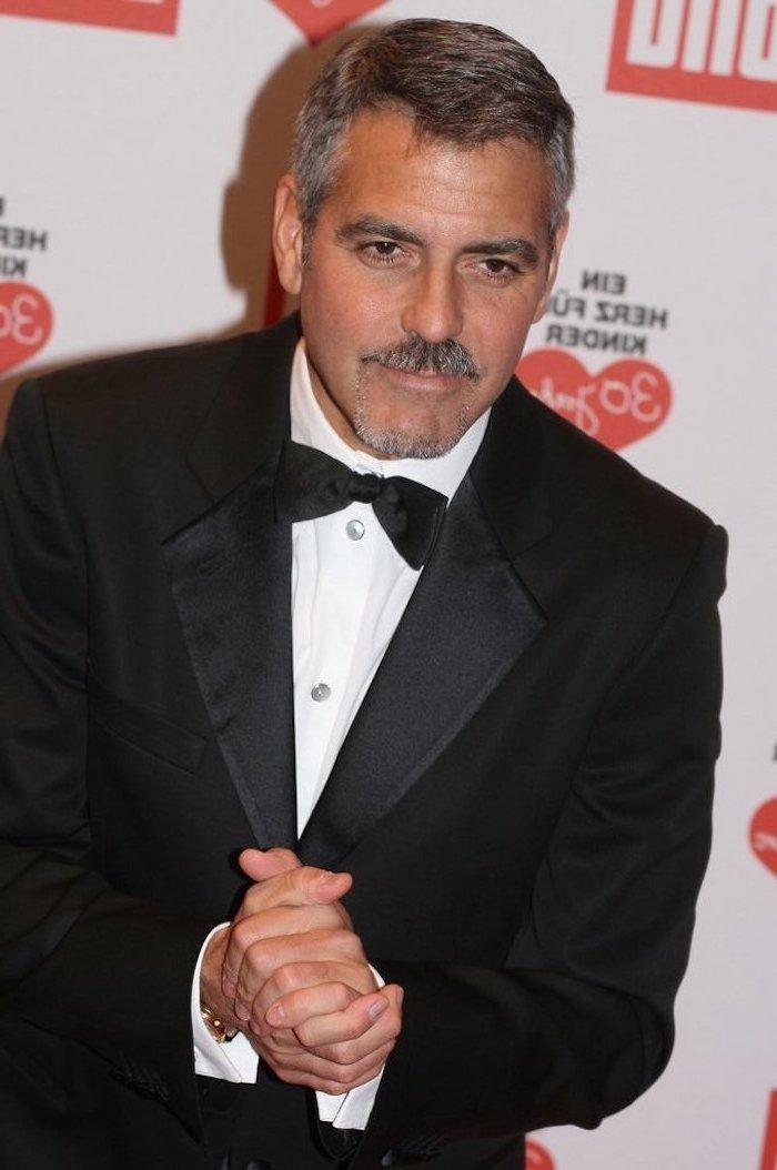 George Clooney schick und elegant wie immer, Kinnbart und Moustache, schwarzer Anzug mit weißem Hemd und Fliege