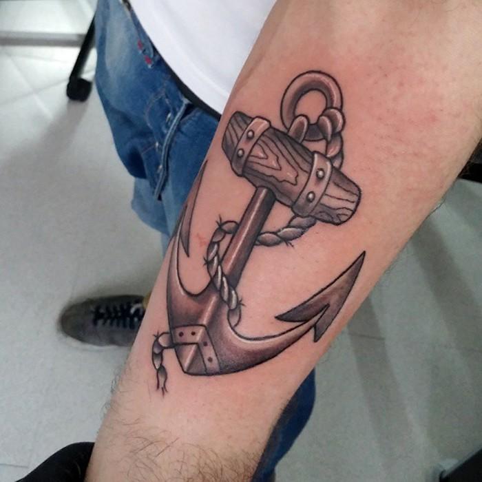 anker bedeutung, mann mit realistischer schwarz-grauer tätowierung am arm