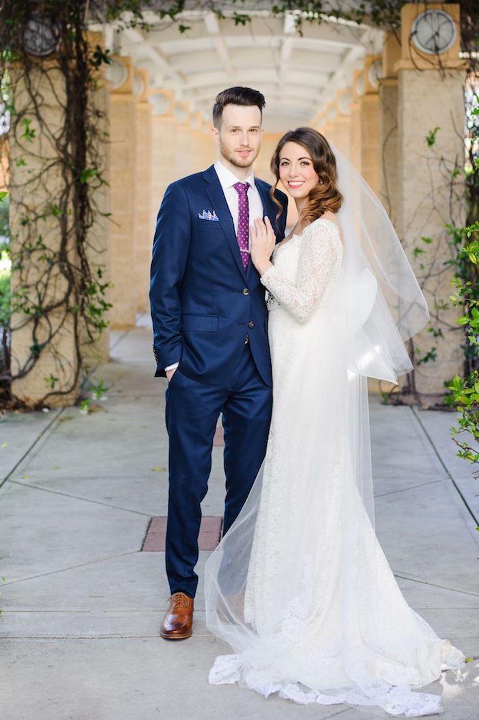 blauer anzug braune schuhe für den stilvollen outfit eines bräutigams lila krawatee und schöne braut mit langem weißen kleid spitze ärmeln