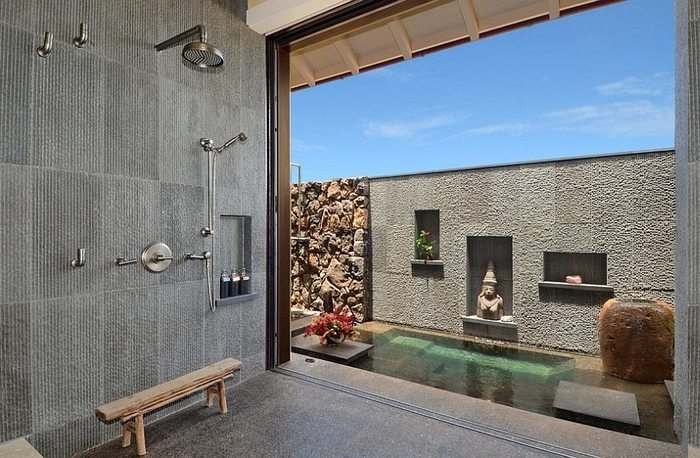Designer Badezimmer im asiatischen Stil mit Übergang zum Außenbereich, Regendusche montiert an der Wand, Wandnische mit drei Seifenbehälter, Außenbereich mit Buddha-Statue, kleinem Teich und Natursteinwand