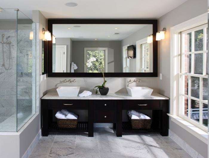 riesengroßer Wandspiegel mit Massivrahben über den beiden Waschbecken, Waschtisch mit zwei Becken, zwei Flechtkörbe für saubere Handtücher, zwei Wandlampen auf beiden Seiten des Spiegels