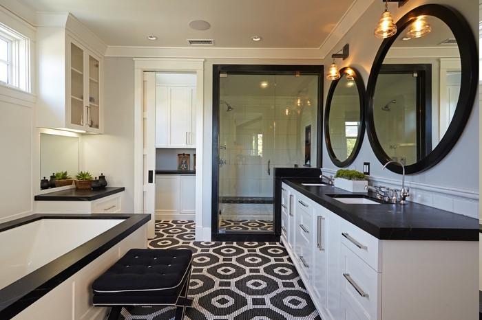 indirekte LED-Beleuchtung, zwei runde Spiegel mit schwarzem Holzrahmen, weißer Waschbecken-Unterschrank, schwarzer Polsterhocker vor der Einbauwanne, Boden mit kleinen schwarzen und weißen Fliesen