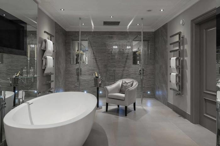 elegante Badeinrichtung - Leder-Armstuhl in silberner Farbe mit einem grauen Deko-Kissen, Tuchaufwärmer an beiden Wänden, zwei Duschen mit dekorativen Nischen, Tür aus Massivholz