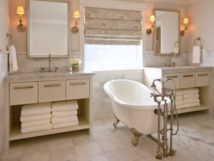 freistehende Badewanne mit vergoldeten Beinen mit Vintage-Motiven, Fensterrollos mit Blumenmotiv, Spiegel mit elegantem schmalen Rahmen, Haufen weiße Badtücher, weiße Blumen in einer Glasvase