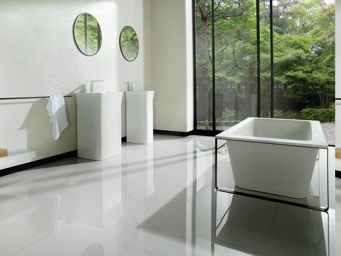 Badeinrichtun im minimalistischen Stil, zwei freistehende Waschbecken aus Keramik mit zwei runden Wandspiegeln darüber, Raumteiler aus Glas, Aussicht zum Wald
