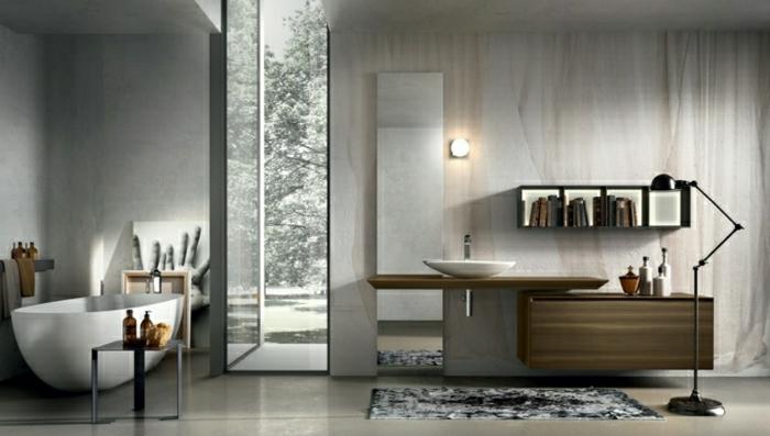 schmales Badfenster rechts von der Badewanne, kleiner Metalltisch für Badöle, grauer Musterteppich vor dem Waschbecken, Bücherregal mit dekorativer Funtion