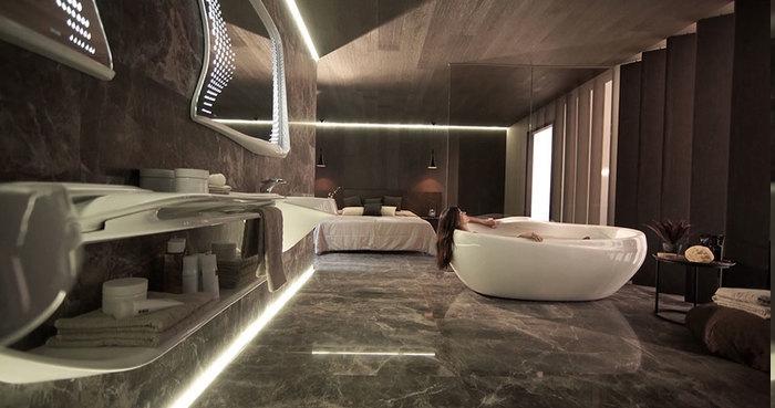 Designer Badezimmer mit indirekter Led-Beleuchtung, zwei moderne Spiegel mit LED-Lampen, Decke mit Holzverkleidung, Frau in der Badewanne