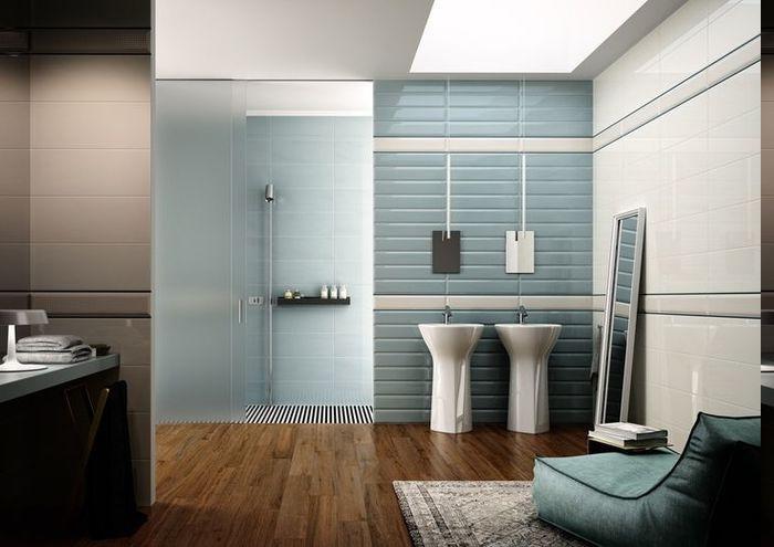 schmale Wandfliesen in blauer Farbe, Decke mit Fenster für mehr Naturlicht, Sessel mit blauem Bezug, Duchregal aus Holz, Wanddeko aus Fliesen