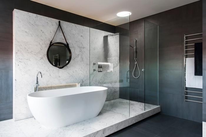 Tuchaufwärmer an der Wand montieren, schwarzer Gesichtstuch und weißer Badetuch, Badezimmer auf zwei Ebenen mit Marmorstufen