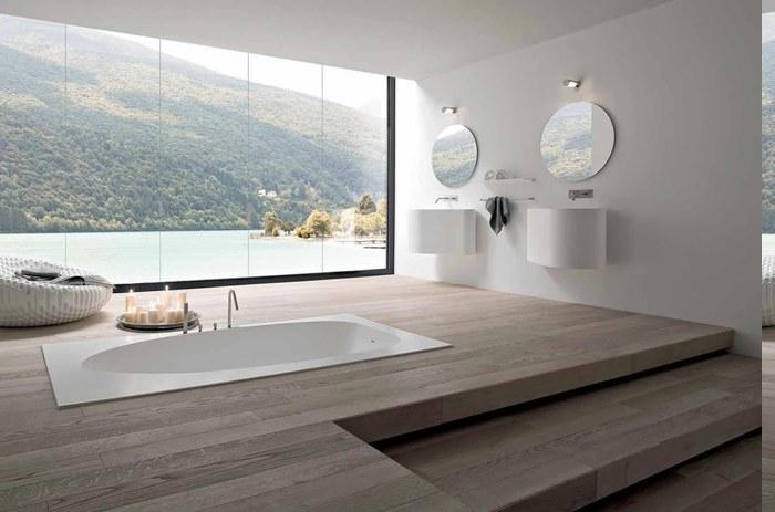 zwei Holzstufen führen zur zweiten Ebene mit Einbauwanne, Designer-Sessel neben dem Fenster mit Gebirgaussicht, Fenster bis zum Boden