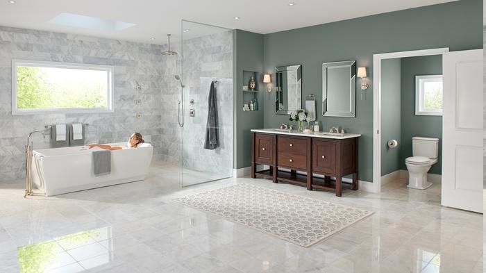 Frau liegt in der Badewanne unter dem Fenster, Duschraum mit Glas-Trennwand, Holzschrank mit runden Griffen, zwei Badspiegel mit Spiegelrahmen und zwei Wandlampen daneben, Toillete mit kleinem Fenster