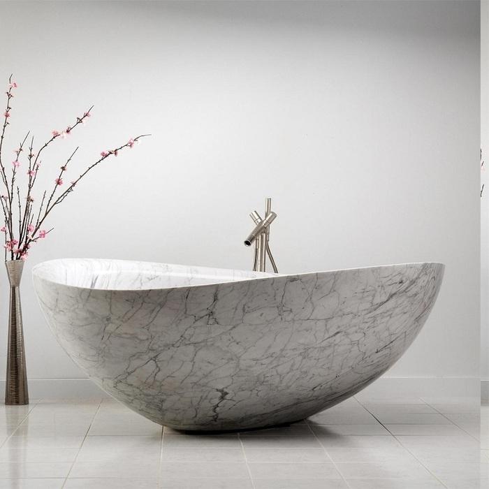 ovale Badewanne aus weißem Marmor, dekorative Vase mit purem Design mit einem Baumzweig mit rosa Blühten