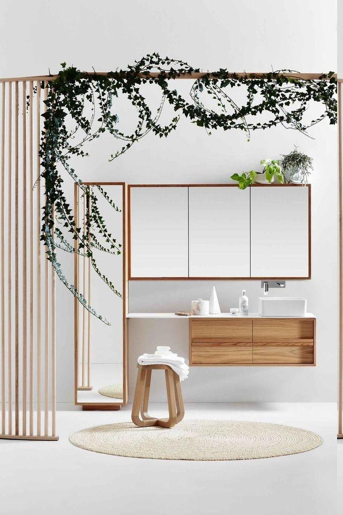 Raumteiler aus Holzgittern mit einem Rankgewächs, runder Teppich in Cremeweiß, Hocker aus Holz, Spiegelschrank mit einer grünen Pflanze darauf
