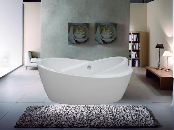 Trennwand mit Marmoroptik, zwei Bilder mit einer weißen Rose, Designer-Badewanne mit untypischem Design, grauer Plüschteppich, weiße Couch aus Leder, Bücherregal voll von Büchern
