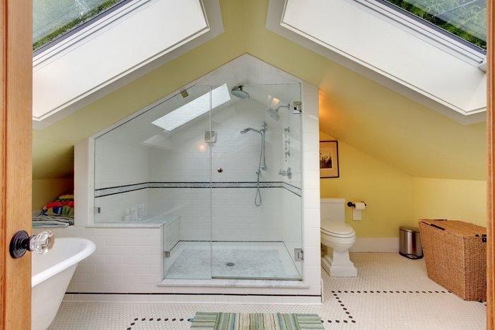 Dachwohnung mit Badezimmer am zweiten Stock, zwei große Dachfenster, kleiner Musterteppich mit Streifen, Tür aus Holz, Wöschekorb mit Deckel, Papierkorb mit Deckel