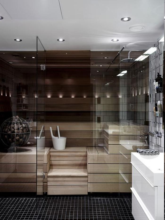 Sauna mit LED-Licht, Rainbow Shower, kleine schwarze Bodenfliesen, drei Kosmetikregale aus Metall, kleine Led-Lampen an der Decke