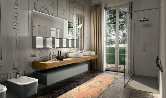 Mustertapete mit antiken Elementen, Waschtisch aus Holz, langer Vorhang für Glastür, Glastür mit weißem Rahmen, Regendusche mit zarten Wasserstrahlen, schmaler Teppich mit marokkanischen Motiven