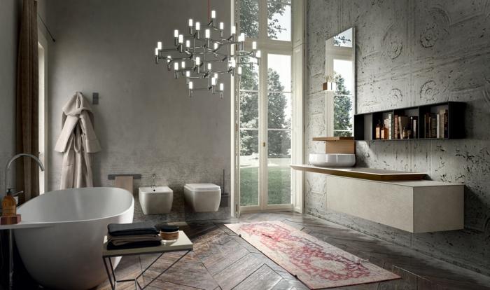 Morgenmantel an der Wand aufhängen, Tisch für Badewanne mit ein Haufen Tücher, kliner marokkanischer Teppich, Wand mit Mustretapete, Designer-Kronleuchter aus Glas, Tür zum Gartenbereich