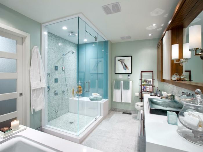 Duschkabine mit Sitzbank, Wandnische mit Spiegel mit Lampen, dekorative Glasschüssel mit Deckel, abstraktes Bild an der Wand, Musikboxen an der Decke