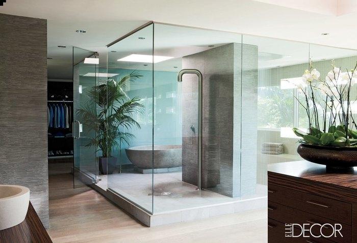 Badkabine mit Badewanne aus Naturstein, große Palme in der Ecke, offener Kleiderschrank, Bad mit Glaswand