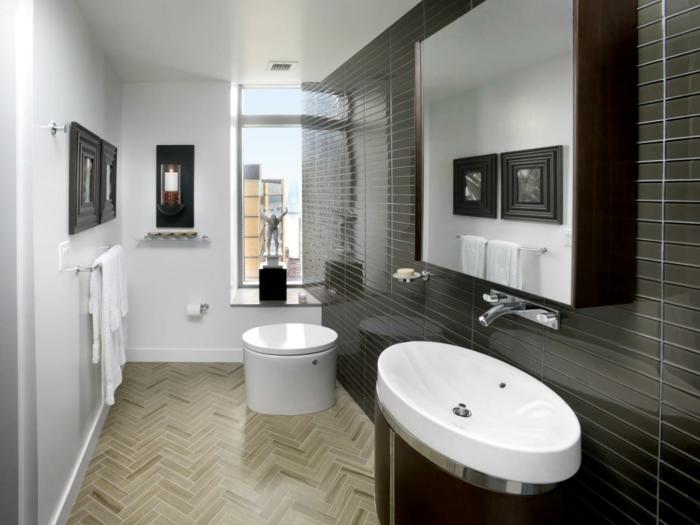dünne braune Badfliesen in Kombination mit beige Fliesen, Toilette mit runder Form, Kerzenhalter an der Wand, Bilder mit Holzrahmen