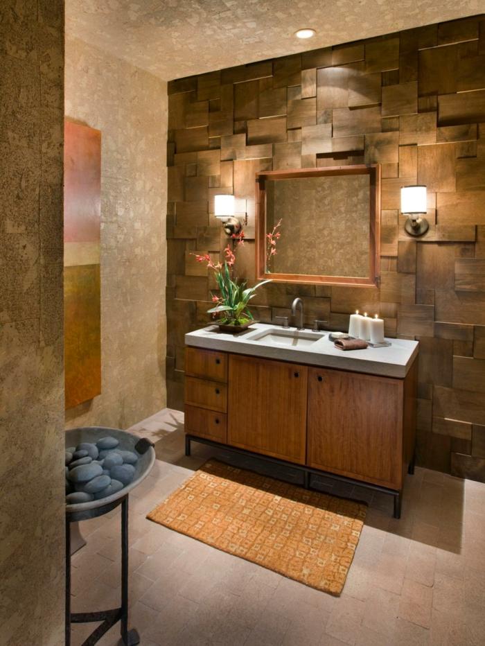 Wand mit Korkverkelidung, Wand mit Holzpaneelen verkleiden, Lampen an der Wand montieren, orangenfarbene Fußmatte mit Muster, viereckiger Spiegel mit Holzrahmen, drei Kerzen auf dem Waschtisch, Dampfkassel für Sauna mit Lavasteinen