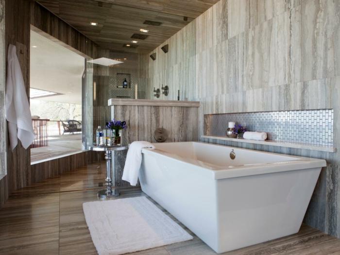 Bad mit Terrassenübergang, Fliesen mit Holzoptik, weiche weiße Fußmatte für Badewanne, Marmor-Trennwand, runder Metalltisch mt Blumendeko