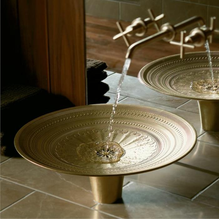 kleine Waschbecken - rundes Becken aus Edelstahl mit Goldabdeckung und Verzierungen, Wasserhahn mit Goldabdeckung montiert an der Spiegelwand, Wand mit Holzverkleidung, Waschtisch mit Terrakottafliesen