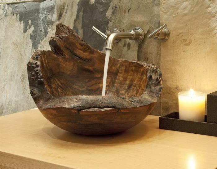 freistehender Holzbecken mit unregelmäßiger Form, Kupferhahn mit Wandmontage, Tisch aus hellem Holz, Wand mit Steinoptik