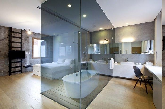 1-Zimmer-Wochnung mit Badkabine aus schwarzem Glas, Spiegel mit Lampe dahinter, schwarzer Stul aus Plastik, Doppelbett mit weißen Laken
