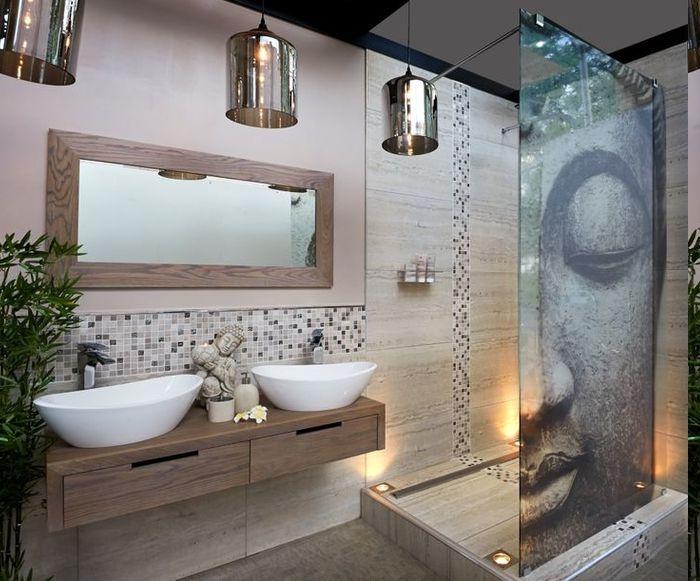 Duschraum mit Glas-Trennwand mit Buddha-Motiv, zwei ovale Keramikbecken mit Unterschrank aus Holz und eine Buddha-Statue in der Mitte, schmaler Spiegel mit Holzrahmen, drei Industrial-Kronleuchter mit Kupferüberzug, Mosaikfliesen als Akzent