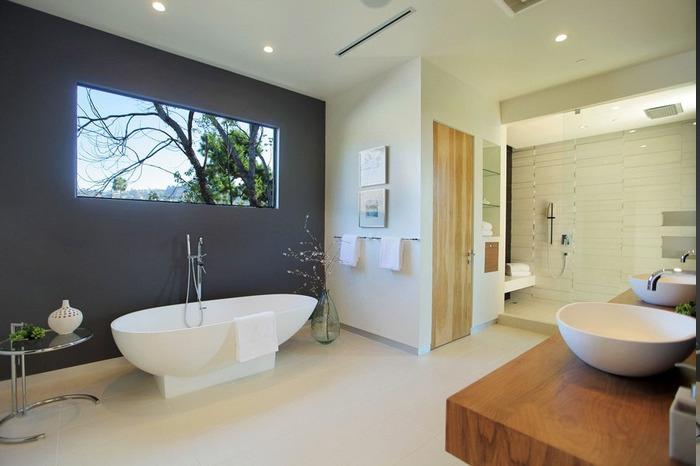 schwarzgestrichene Wand mit Fenster, runder Designer-Tisch aus Metall mit einer weißen Vase, große Glasvase mit frischen Zweigen, Waschtisch aus massivem Holz, Einbauregale aus Glas