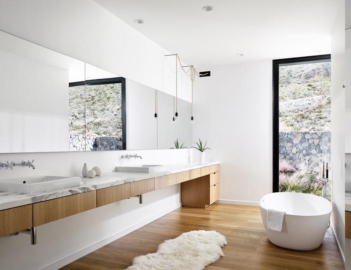 Tichplatte aus weißem Marmor, Spiegel an der ganzen Wand, Lautsprecher an der Decke, weiche Plüschmatte in Weiß, Aussicht zum Garten