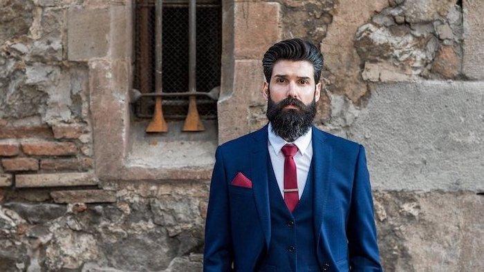 Herr mit Vollbart und mittellangen schwarzen Haaren, eleganter Anzug in Dunkelblau, weißes Hemd und rote Krawatte