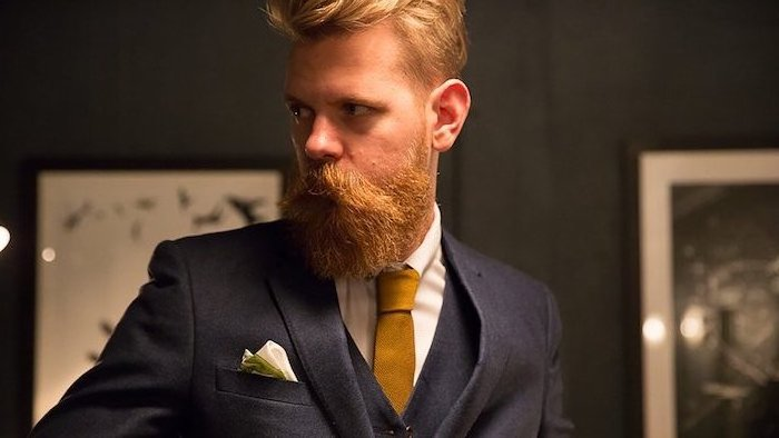 Eleganter Herr mit Kurzhaarfrisur und Vollbart, schwarzer Blazer, weißes Hemd mit dunkelgelber Krawatte