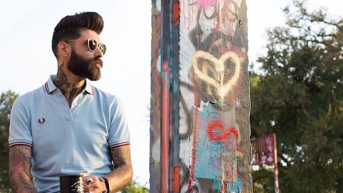 Casual Outfit und schicke Frisur, hellblaues T-Shirt mit roten Kanten, viele Tattoos und Schmuck