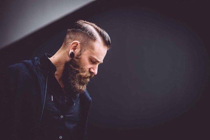 Mann mit Kurzhaarfrisur und Vollbart, schwarzes Hemd und schwarze Jacke, auffällige Ohrringe