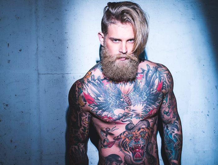 barttypen langer lockiger blonder bart mann mit tattoos bunte gestaltung auf dem körper blonde haare sidecut die eine seite lang halten und die andere ganz kurz