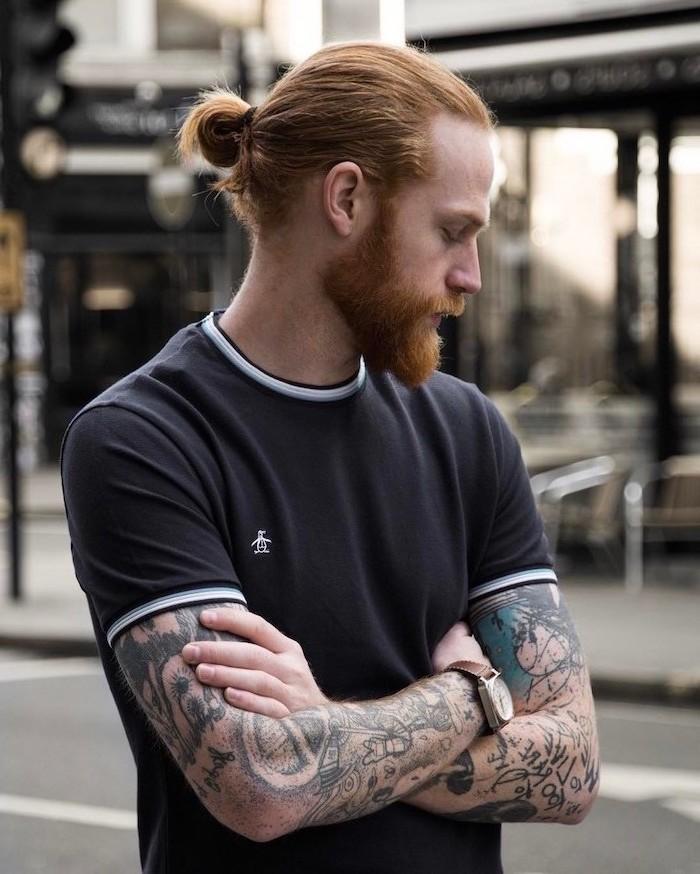 Mann mit langen naturroten Haaren und Vollbart, viele Tattoos an den Armen, schwarzes T-Schirt mit weißen Kanten