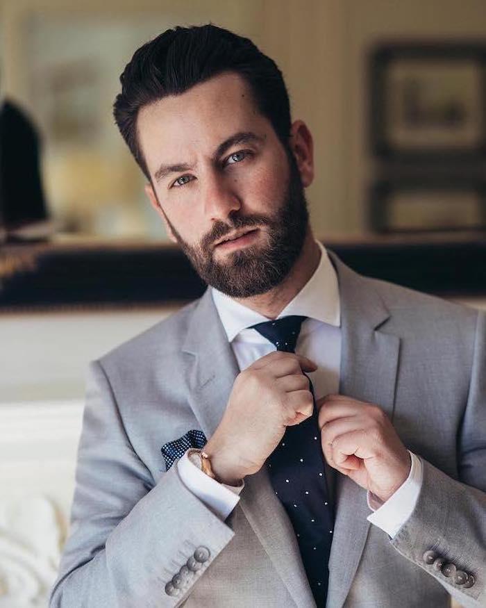Mann im schickem Anzug, grauer Blazer, weißes Hemd mit dunkelblauer Krawatte, Kurzhaarfrisur und Vollbart