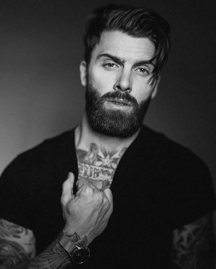 Herr mit mittellangen glatten Haaren und Vollbart, viele Tattoos, schwarzes T-Shirt mit kurzen Ärmeln