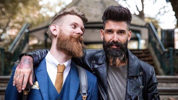 Zwei Herren mit Bart, einer von ihnen in blauem Anzug, der andere trägt T-Shirt und schwarze Lederjacke