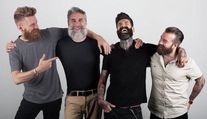 Vier Herren mit Vollbart und Kurzhaarfrisuren, Casual Look, T-Shirts und Jeans, viele Tattoos