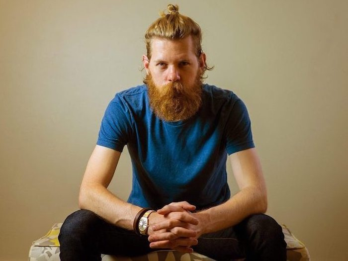 Herr mit langen naturroten Haaren und Hipster Bart, Casual Look, blaues TShirt und schwarze Hose