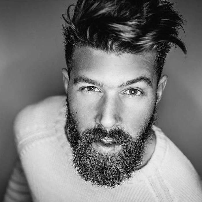 Hipster Bart und mittellange Haare, große braune Augen, weißer Pullover mit langen Ärmeln