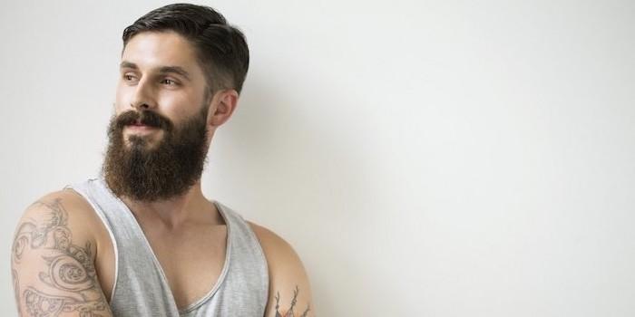 Hipster Bart und Kurzhaarfrisur, graues Top und viele Tattoos an den Armen