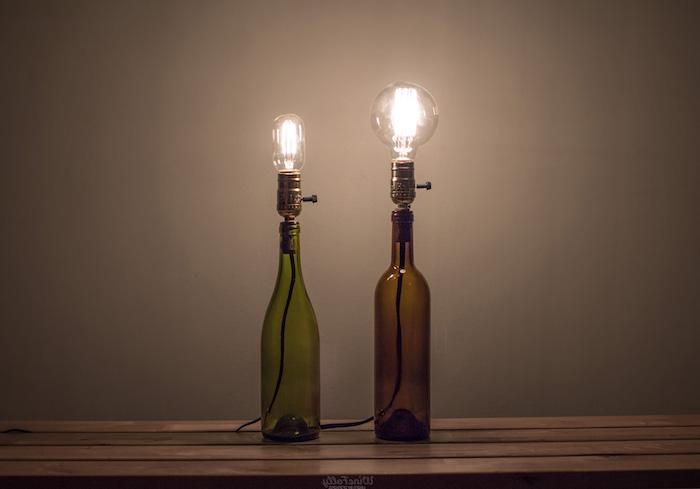 flaschenlampe selber bauen - zwei grüne und braune glasflaschen mit leuchtenden glühbirnen und tisch aus holz