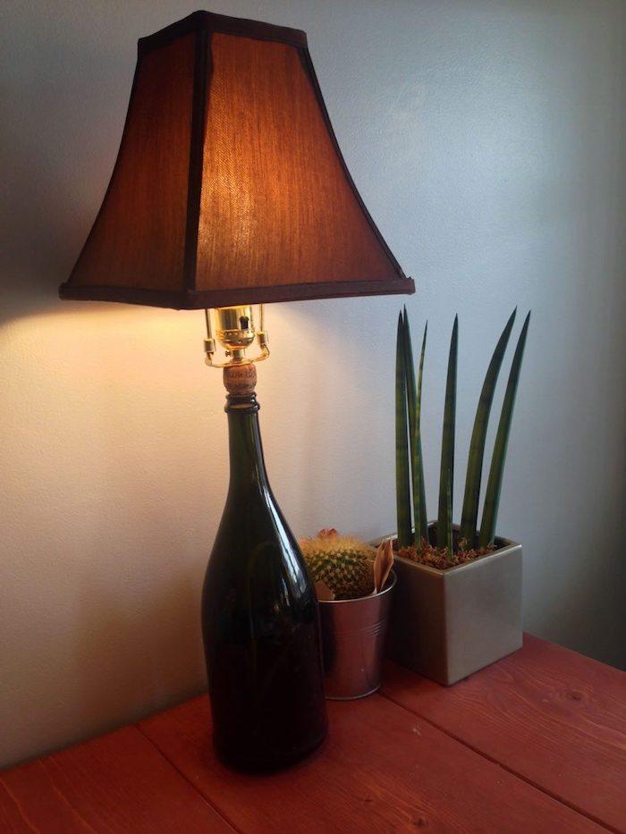 tiasch aus holz - zwei blumentöpfe mit grünen pflanzen - eine lampe aus einer schwarzen großen flasche - flaschenlampe selber bauen