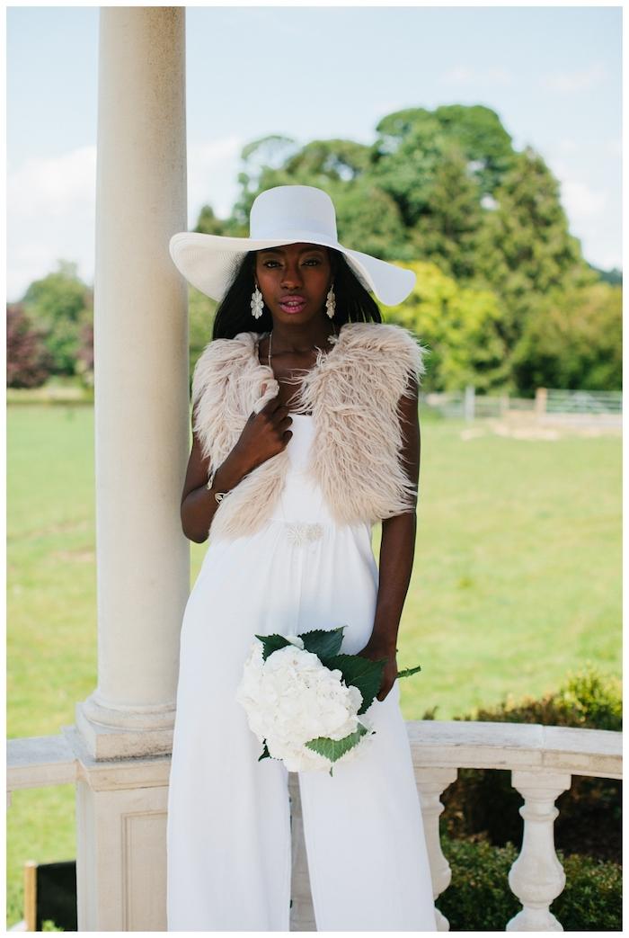 weißer jumpsuit damen mode zum inspirieren hochzeitsparty komfortable bekleidung beige weste großer hut blumenstrauß
