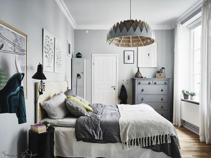 Schlafzimmer mit hellgrauen Wänden und weißer Zimmerdecke, Bett mit Kopfbrett aus Holz, viele Kissen in Graunuancen, runder schwarzer Tisch mit drei Büchern darauf, Kopfbrett mit beweiglicher Leselampe, graue Holzkommode mit metallen Griffen, schmaler weißer Schrank mit einer grünen dekorativen Vase darauf, Designer-Kronleuchter aus Holz, großes Fenster mit zwei grünen Pflanzen am Fensterbank